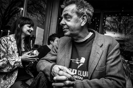 Man with rigged face and spiky hair in tweed jacket sitting at bar with people in background. Shakespeare's Head pub Brihjton UK. Black and white nightlife scene, character portrait, documentary © P. Maton 2016 eyeteeth.net