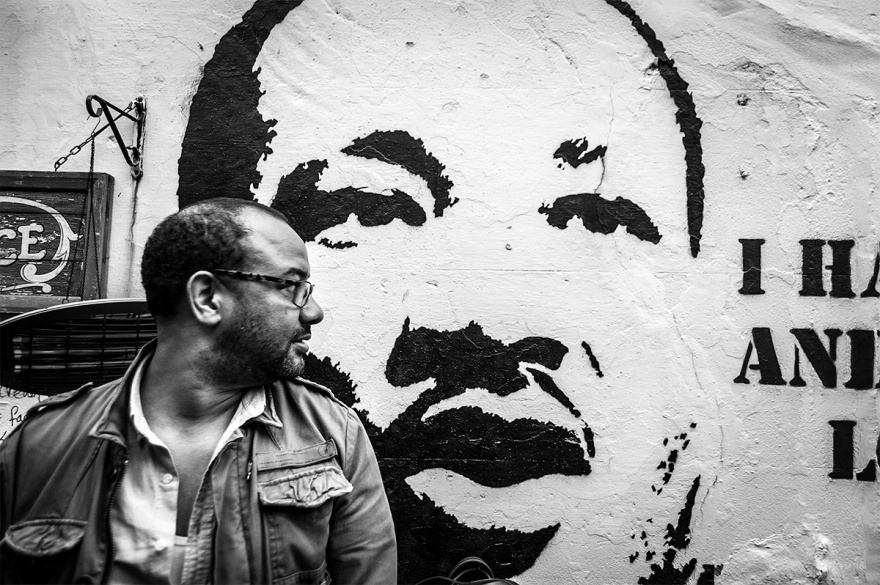 Man standing in front of wall street art stencil of Martin Luther King.  Black and white urban street documentary photography.  © P. Maton 2016 eyeteeth.net