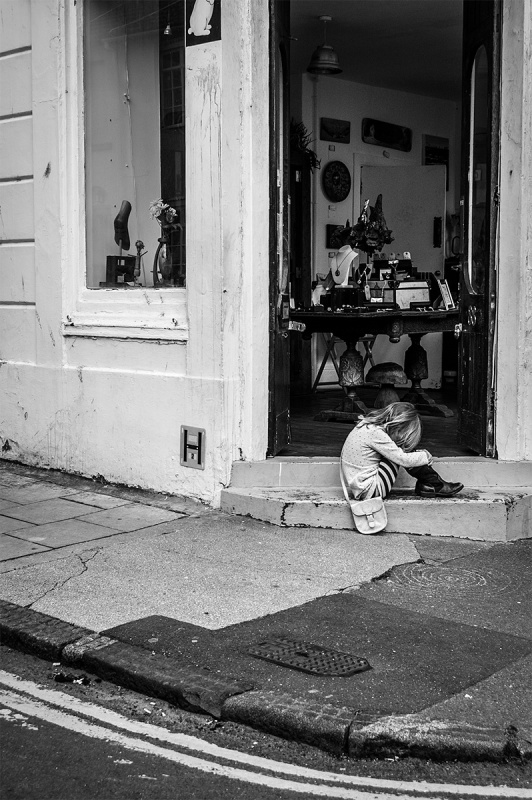 Upset young girl with shoulder bag sitting on step in shop doorway. Gloucester Road Brighton UK. Urban street photography. ©P. Maton 2016 eyeteeth.net