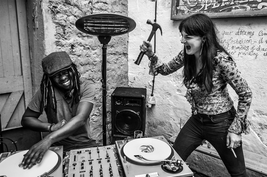 DJ with dreadlocks and cap smiling as woman with long hair brandishes hammer . Musical differences at the party. Black and white photograph, fun comedy documentary. © P. Maton 2016