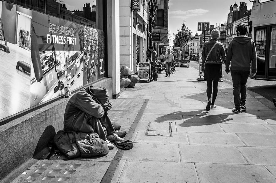 Homeless man in hood bring head in knees as couple walk by hand in hand. Queens Road, Brighton UK. Sussex urban street photography, despair. © P. Maton 2016 eyeteeth.net