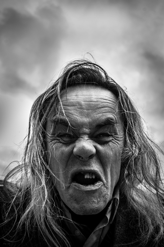 Man with weathered face, missing teeth and long hair roaring in anger at the camera. Oxfordshire UK. Black and white dramatic documentary portrait. © P. Maton 2016 eyeteeth.net