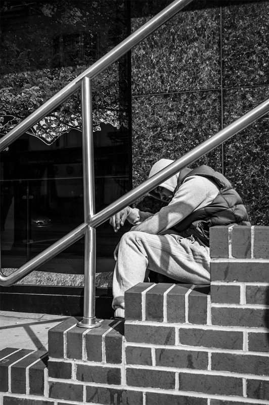 Drugged man with hoody over head possibly after taking Heroine sitting on steps nearly sleeping. Queens Road Brighton UK. Black and white urban street photography. © P. Maton 2016 eyeteeth.net