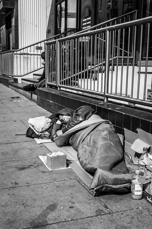 Homeless man sleeping on street by railings. Queen's Road Brighton UK. Black and white urban street photograph. © P. Maton 2016 eyeteeth.net