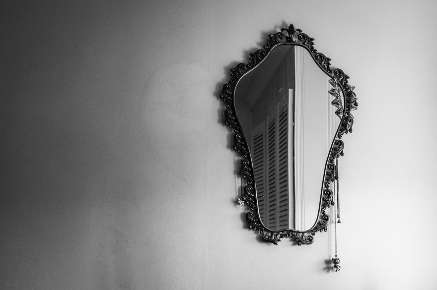 Torso shaped ornate mirror hanging on wall with wardrobe door in reflection. Black and white interior photograph. © P. Maton 2016 eyeteeth.net