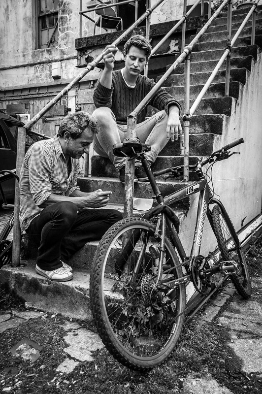 Two men smoking cigarettes sitting on outdoor steps with bicycle in foreground and chair on balcony in background. Farm Road Hove, Black and white urban street photography. © P. Maton 2016 eyeteeth.net