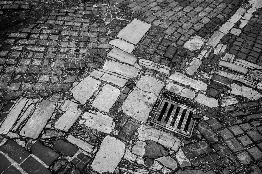 Slotted metal drain cover among chaotic flag stones. abstract urban street photography. Farm Road Hove UK. © P. Maton 2016 eyeteeth.net