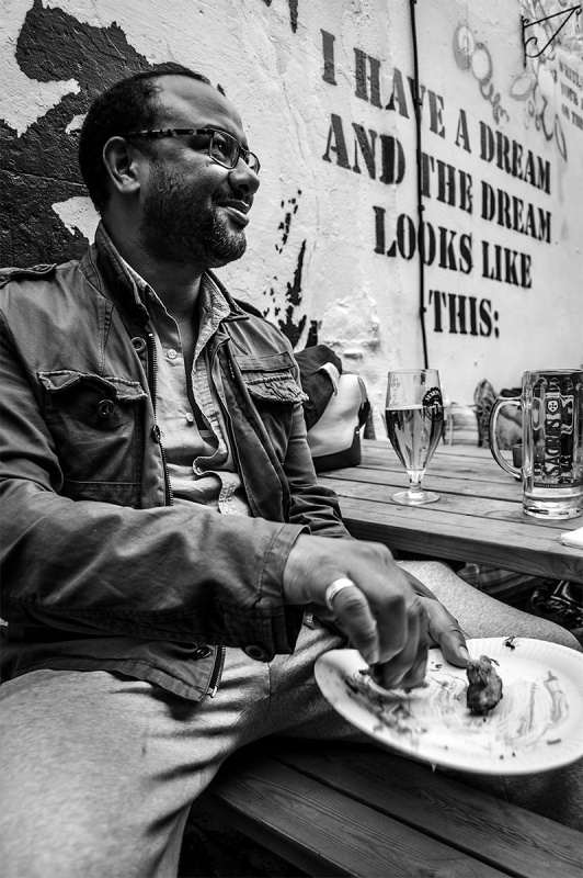 Black man eating food in pub garden with drinks on table and Martin Luther King quote written on wall behind. Brighton UK. Black and white street portrait documentary photograph. © P. Maton 2016 eyeteeth.net