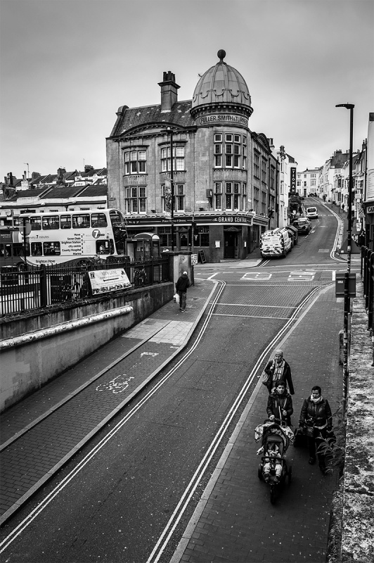 View up Trafalgar Street from Brighton railway station with Grand Central pub and people walking with pram below. Brighton Sussex UK. Black and white urban street documentary photograph. © P. Maton 2016 eyeteeth.net