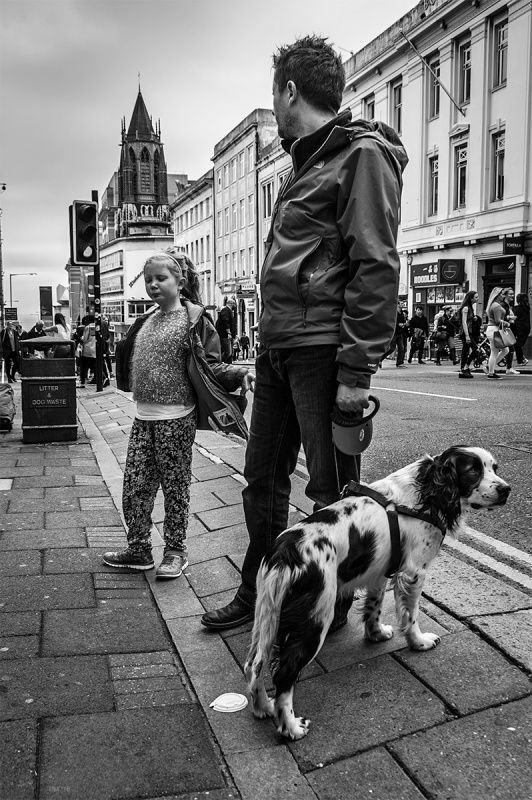 Girl putting on coat while father looks down street towards sea holding spaniel on a lead. West Street Brighton Sussex UK. Black and white urban street photograph. © P. Maton 2016 eyeteeth.net.