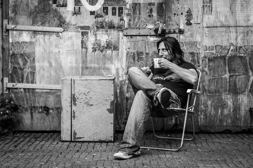 Man drinking from mug sitting in deck chair in front of painted an weathered garage doorways. Farm Road Hove UK. Black and white urban street photography. © P. Maton 2016 eyeteeth.net