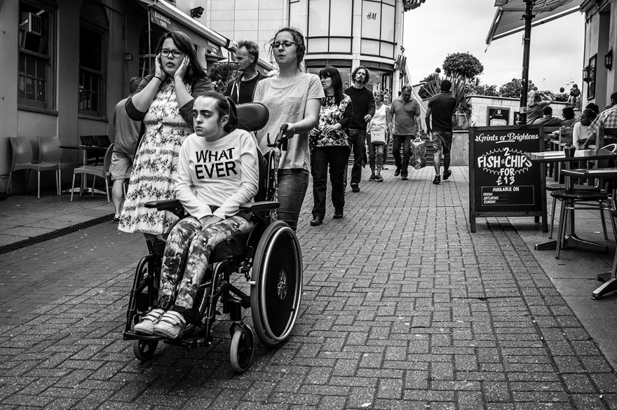 Girl in wheelchair wearing teeshirt saying WHAT EVER on from being pushed down Cranbourne Street Brighton UK. Black and white urban street scene, street photography. © P. Maton 2015 eyeteeth.net