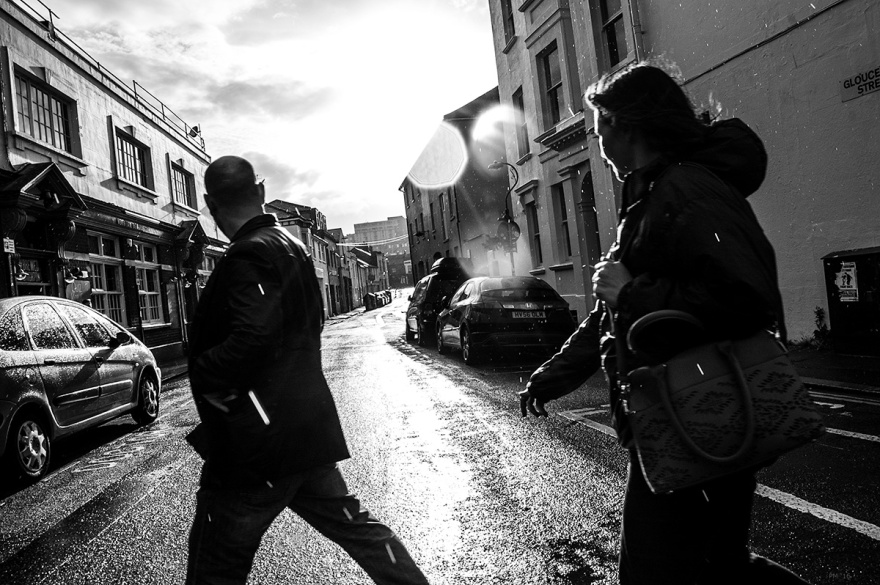 Silhouettes of people crossing wet road in sunshine and rain, Gloucester Street Brighton UK. Urban street photography black and white. © P. Maton 2016 eyeteeth.net