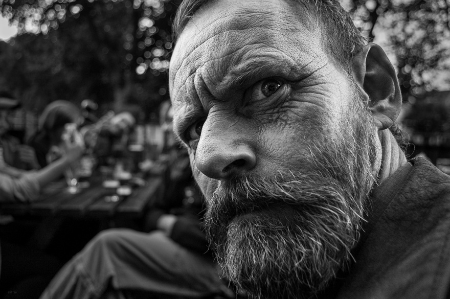 Man with beard staring into cameral while frowning. Twilight portrait black and white photograph. Brighton UK. © P. Maton 2016 eyeteeth.net