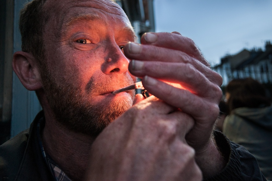 Man lighting cigarette with glow from flame on face and hands. Brighton UK portrait photograph. © P. Maton 2016 eyeteeth.net