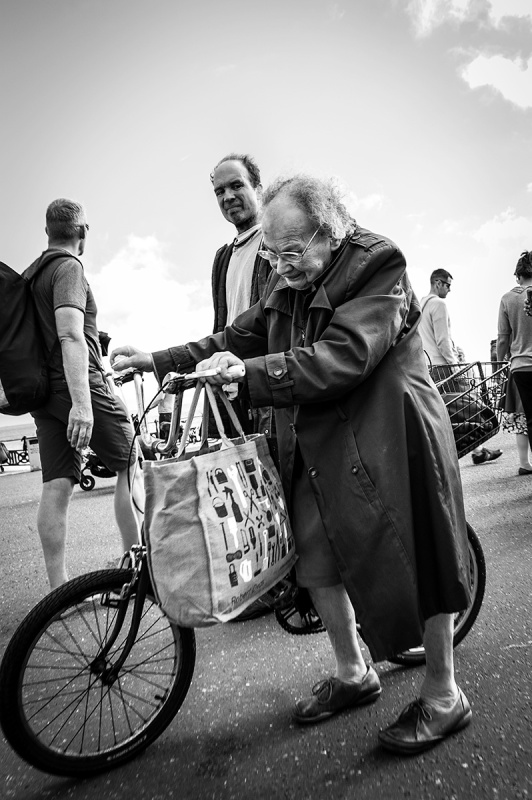 Hunched old woman pushing bicycle with full shopping bag on handlebars while her middle aged son looks on from behind, hove seafront scene with people passing in background. Hove Lawns, Sussex UK. Street photography black and white. © P. Maton 2016 eyeteeth.net