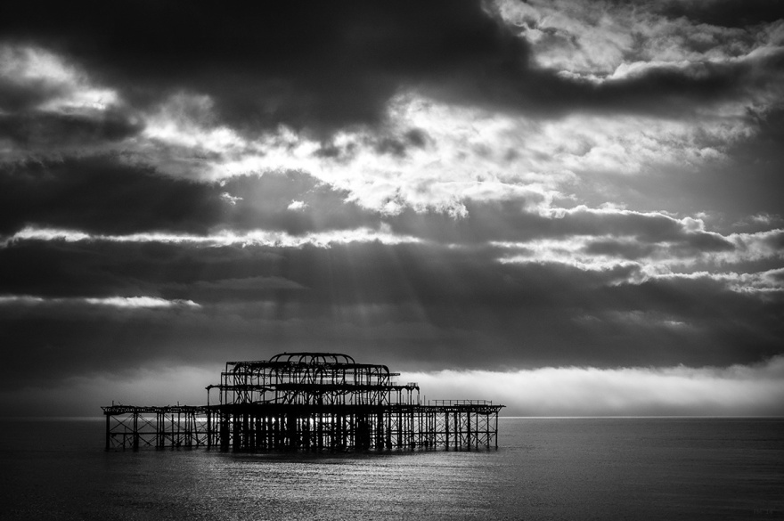 Ruined framework of abandoned West Pier Brighton UK with dramatic clouds and sun rays shining on water. Black and white seascape, moody atmospheric. © P, Maton 2014 eyeteeth.net