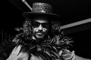 man in sun glasses wearing straw boater and feather boa looking at camera, flamboyant pimp costume nightlife Brighton UK. Black and white portrait © P. Maton 2016 eyeteeth.net