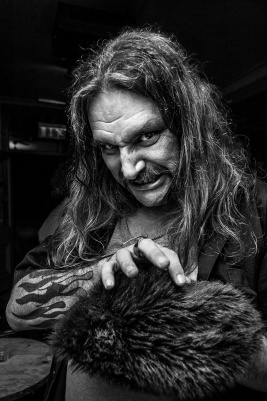 moustached man with long hair, tattoos and claw like hand reaching over a fake fur hat while grimacing in a sinister fashion at the camera. Black and white portrait. © P. Maton 2016 eyeteeth.net