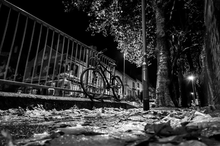 Bike locked to railings, autumn, leaves, rain, night, street, urban. Black and white urban street photography landscape, night and rain. Chatham Place Brighton UK. © P. Maton 2016 eyeteeth.net