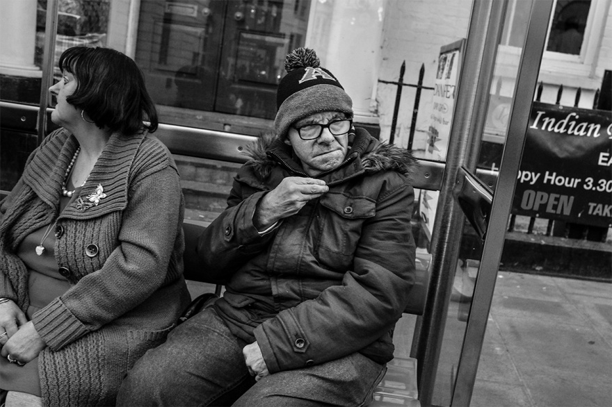 Couple sitting at bus stop with warm coats and wooly hat. North Street Brighton UK. Urban street photography. © P. Maton 2016 eyeteeth.net