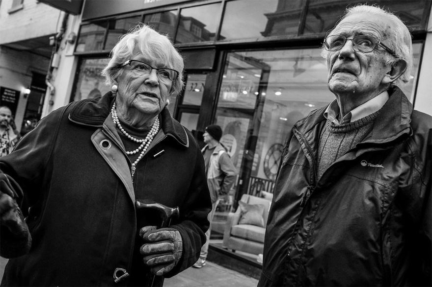 Elderly couple standing in North Street Brighton UK. Urban street photography, black and white landscape. © P. Maton 2016 eyeteeth.net