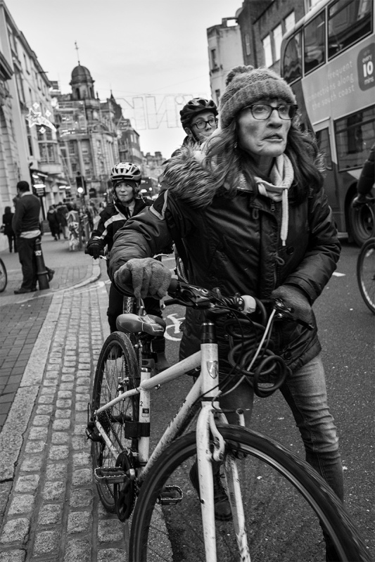woman pushing bicycle on North Street Brighton UK street photography. Black and white portrait. © P. Maton 2016 eyeteeth.net