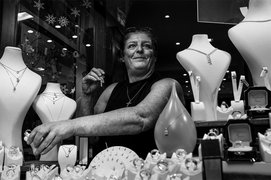 Smiling woman in jewellery shop window reaching for a ring. Black and white street photography South Lanes_Brighton UK. © P. Maton 2016 eyeteeth.net