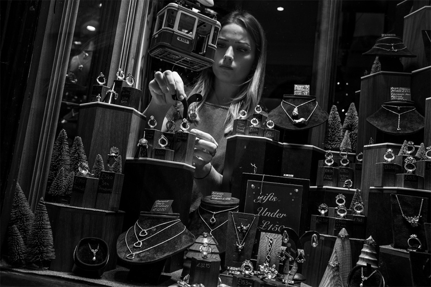 Girl in jewellery shop window arranging earrings. Black and white street photography South Lanes_Brighton UK. © P. Maton 2016 eyeteeth.net