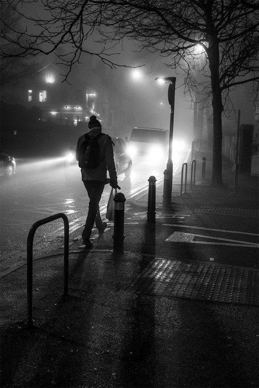 Man in bobble hat walking up Chatham Place, Brighton UK in fog with approaching traffic at night. Black and white street photography portrait ©P. Maton 2016 eyeteeth.net