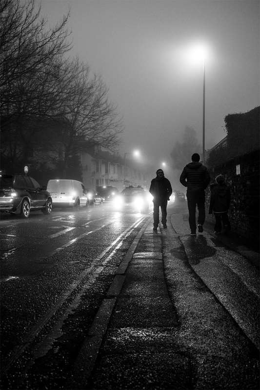 People passing on pavement  silhouetted by car lights  with wet road and fog. Urban street photography. Brighton Sussex UK. © P Maton 2017 eyeteeth.net