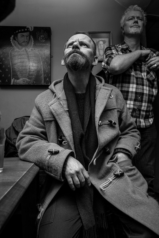 Man with beard in duffel coat looking upwards into light, Shakespeares Head Pub Brighton UK. Black and white nightlife documentary portrait photography. © P. Maton 2017 eyeteeth.net