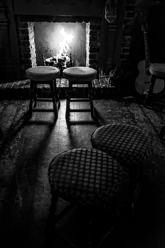 Fireplace with stools illuminated by firelight. Royal Sovereign Pub Brighton UK. Nightlife urban photography black and white. © P. Maton 2017 eyeteeth.net