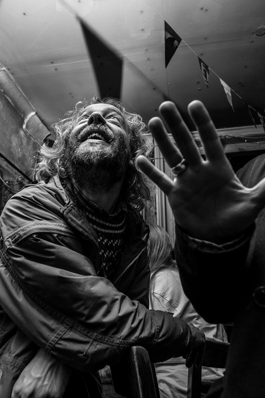 Grinning man with beard looking up into light with hand in foreground, Shakespeares Head Pub Brighton UK. Black and white nightlife photography. © P. Maton 2017 eyeteeth.net