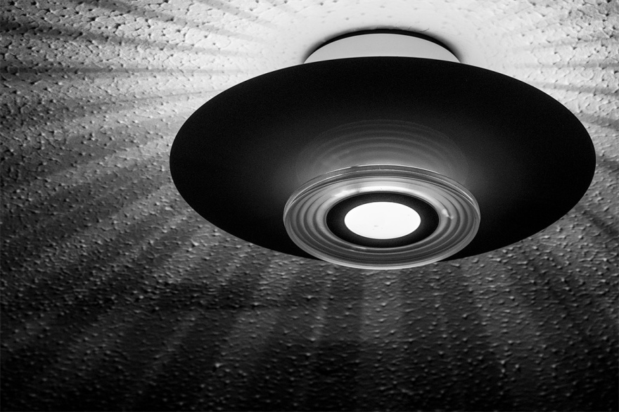 Lamp shade casting rays across art ceiling looking like alien UFO flying saucer.  Black and white landscape abstract. © P. Maton 2017 eyeteeth.net