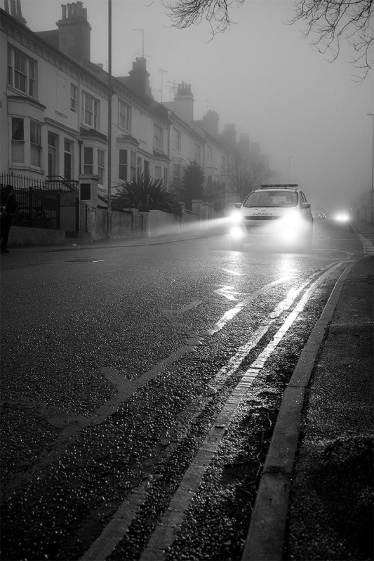 Police car on foggy street with headlights  reflected on wet road in evening. Chatham Place Brighton UK. Black and white urban street photography documentary. © P. Maton 2017 eyeteeth.net