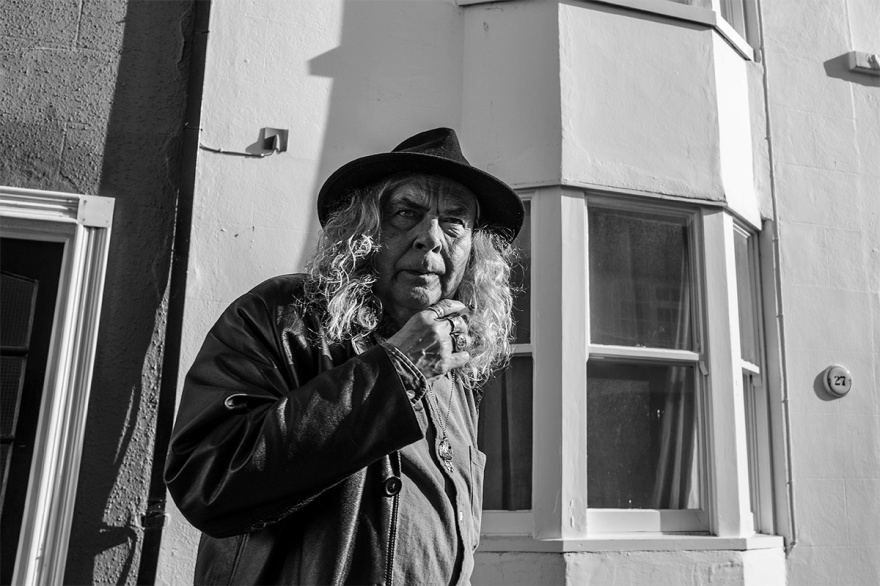 Smoking man with long curly hair and fedora hat in front of houses on Cheltenham Place Brighton UK.  Urban street photography Black and white landscape. © P. Maton 2017 eyeteeth.net