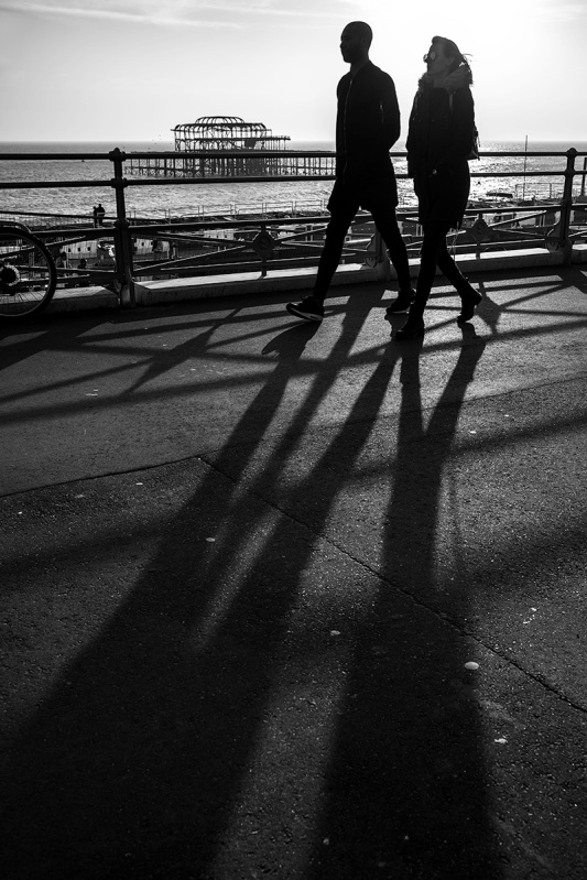 Silhouettes couple casting long shadows walking on seafront  Kings Road Brighton with West Pier ruins in background. Black and white urban street photography. © P. Maton 2017 eyeteeth.net