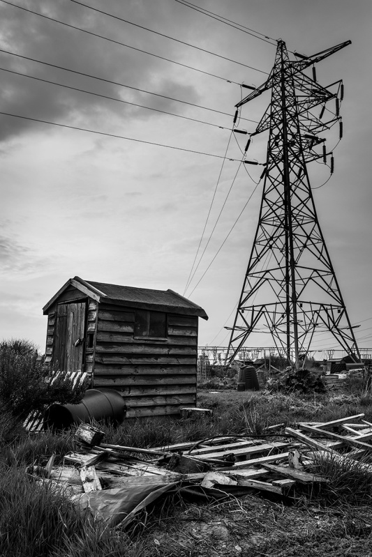Allotment shed with electricity pylon in background and smashed wooden pallet in foreground. Black and white documentary photograph portrait urban Britain. Fujifilm XT-2 XF 16mm 1.4 R WR. Portslade UK. © P. Maton 2017 eyeteeth.net