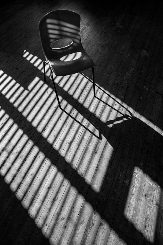 Plastic classroom chair on wooden floor with stripes of sunlight through venetian blind illuminating floor. Black and white documentary photograph Telescombe community church hall Sussex uk. © P. Maton 2017 eyeteeth.net