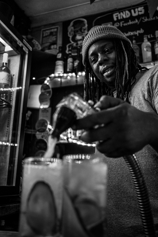 man using soda pump behind bar at Shakespeare's Head pub Brighton uk. Black and white social documentary portrait. Urban nightlife photography @P. Maton 2017 eyeteeth.net