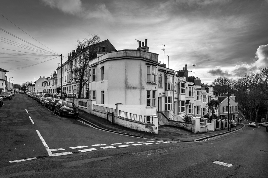 Street corner with terraced houses and  view down roads, early evening sky. Urban documentary landscape photography Howard Place Brighton UK. © P Maton 2017 eyeteeth.net