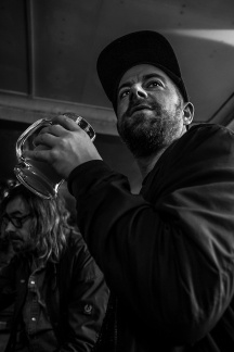 man in baseball cap holding pint tankard of beer at Shakespeare's Head pub Brighton uk. Black and white social documentary portrait. Urban nightlife photography @P. Maton 2017 eyeteeth.net