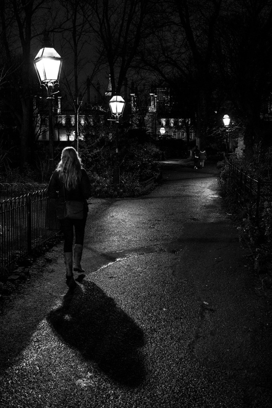 Woman walking through gardens on wet path under lamp light with Brighton Pavilion in background. Moody black and white urban street photography. © P.Maton 2017 eyeteeth.net