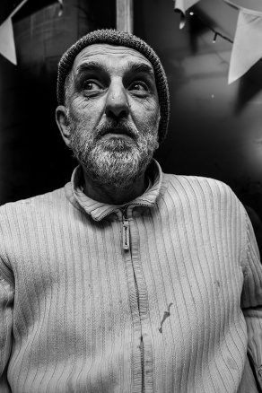 portrait of a bearded man in wooly hat with dirty zip up jumper with window and bunting in background. Characterful face black and white portrait documentary Britain Brighton UK. © P Maton 2017 eyeteeth.net