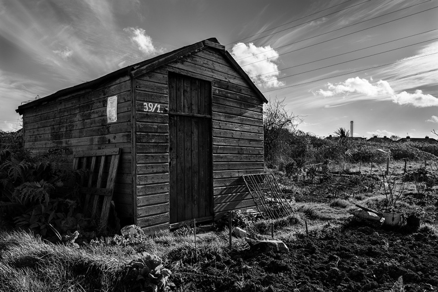 Wooden shed on allotment in Portslade UK with dramatic sky and shadows. Rustic, rural, urban black and white landscape photography. ©P. Maton 2017 eyeteeth.net
