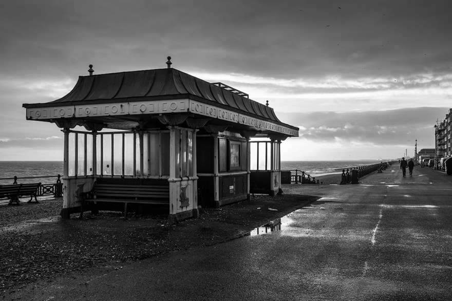 Victorian seafront shelter with benches on Kings Esplanade Hove Sussex UK withe setting sun behind casting light through windows on wet winter evening. Black and white landscape, seaside Britain photography. © P. Maton 2017 eyeteeth.net