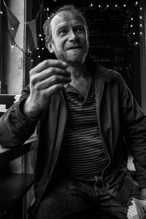 Man raising hand and looking off to the right. Shakespeare's Head pub Brighton UK. Black and white portrait natural light documentary photography. © P. Maton 2017 eyeteeth.net