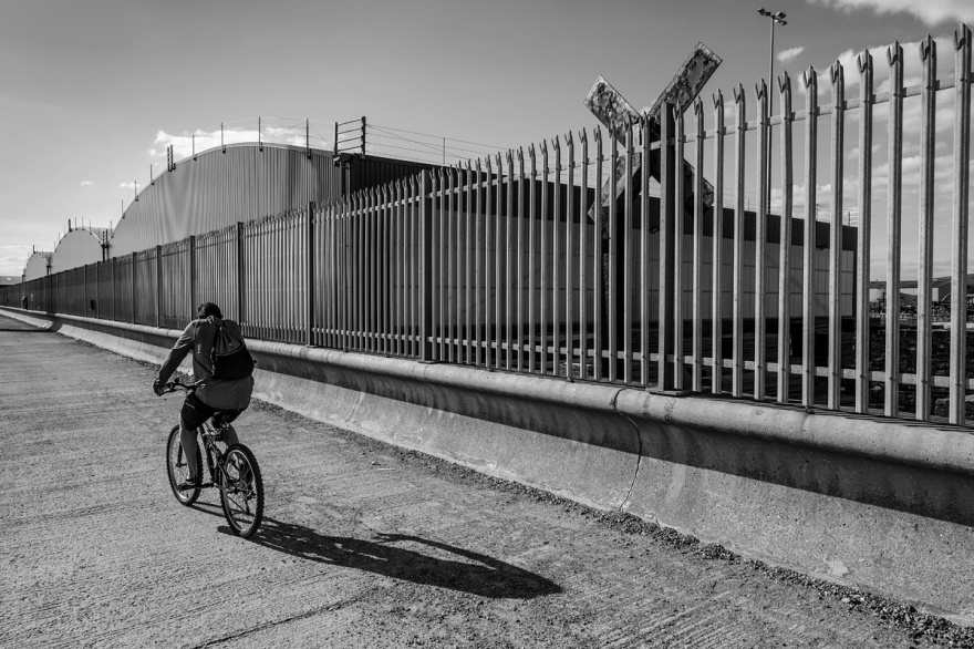 Man cycling along Shroeham Harbour foreshore next to metal railings and warehouses. Shoreham by Sea Sussex UK. Urban documentary street photography black and white landscape ©P. Maton 2017 eyeteeth.net