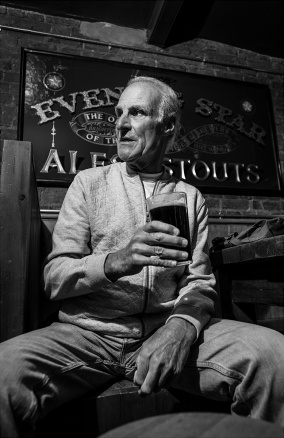 Man with pint of dark ale sitting in front of Evening Star pub sign. Brighton UK. Social documentary nightlife portrait black and white photograph. © P. Maton 2017 eyeteeth.net